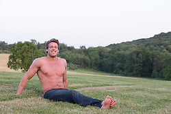 shirtless All American man with blond hair and blue eyes on a grass