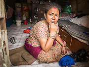 02 AUGUST 2015 - BHAKTAPUR, NEPAL:  A woman sits in her temporary shelter in Bhaktapur. The Nepal Earthquake on April 25, 2015, (also known as the Gorkha earthquake) killed more than 9,000 people and injured more than 23,000. It had a magnitude of 7.8. The epicenter was east of the district of Lamjung, and its hypocenter was at a depth of approximately 15km (9.3mi). It was the worst natural disaster to strike Nepal since the 1934 Nepal–Bihar earthquake. The earthquake triggered an avalanche on Mount Everest, killing at least 19. The earthquake also set off an avalanche in the Langtang valley, where 250 people were reported missing. Hundreds of thousands of people were made homeless with entire villages flattened across many districts of the country. Centuries-old buildings were destroyed at UNESCO World Heritage sites in the Kathmandu Valley, including some at the Kathmandu Durbar Square, the Patan Durbar Squar, the Bhaktapur Durbar Square, the Changu Narayan Temple and the Swayambhunath Stupa. Geophysicists and other experts had warned for decades that Nepal was vulnerable to a deadly earthquake, particularly because of its geology, urbanization, and architecture.      PHOTO BY JACK KURTZ