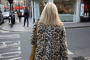 Woman with blonde hair wearing a Leopard print fur coat in Soho, London, United Kingdom.