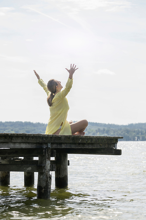 Woman with arms raised sitting on boardwalk at the lake, Ammersee, Upper Bavaria, Germany