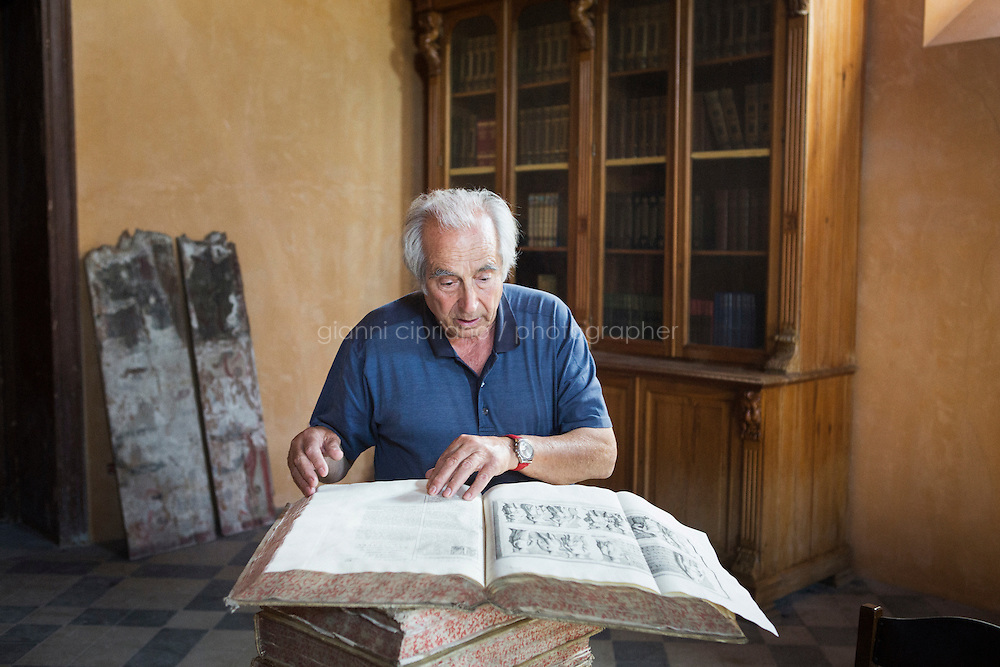 """CASTELVETRANO, ITALY - 29 MAY 2015: Antiquities dealer and olive oil producer Gianfranco Becchina (76) leafs through the pages of an antique book at Palazzo Aragona Pignatelli, a XIII century palace he bought in Castelvetrano, Sicily, Italy, on May 29th 2015.<br /> <br /> Gianfranco Becchina is an Italian antiquities dealer who was taken to trial in Italy of illegally dealing in antiquities. Gianfranco Becchina dealing antiquities in Basel, Switzerland, in the 1970s, and has sold material to major museums including the Louvre, the Boston Museum of Fine Arts, the Metropolitan Museum, the Princeton University Art Museum and the J. Paul Getty Museum. Mr Becchina claims to have stopped dealing ancient art in 1994. Since 1989 he produces the olive oil """"Olio Verde"""" in Tenuta Pignatelli, his estate in the heart of the Valle del Belice, Sicily, where the Nocellara del Belice olive is grown."""