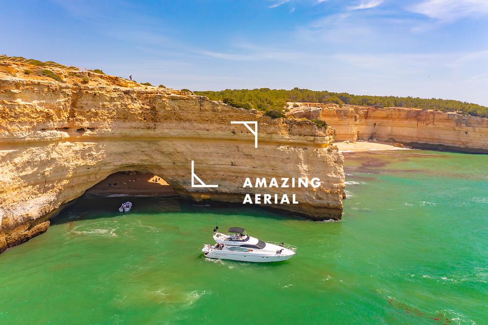 Aerial view of a yacht cruising by Praia da Corredoura beach near the cliffs of Benagil cave in Lagoa, Algarve, Portugal.