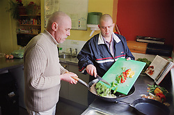 Male residents preparing communal meal in kitchen of homeless hostel for people with learning difficulties,
