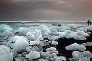 Photographers near piles of icebergs on Jökulsárlón beach in south-east Iceland, at dusk.
