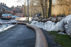 © Licensed to London News Pictures. 16/02/2014. Winchester, Hampshire, UK. A section of the 750m pipe pumping water from Park Avenue in Winchester, Hampshire downstream away from the city into the River Itchen. Work is well underway by Hampshire Fire & Rescue and the Environment Agency to restore the flooded areas back to normality. Photo credit : Rob Arnold/LNP
