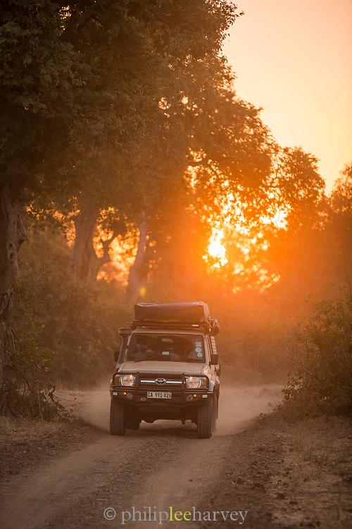 Safari car on dirt road at sunset, South Luangwa National Park Nsefu Sector, Zambia