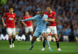 MANCHESTER, ENGLAND - Monday, April 30, 2012: Manchester City's Yaya Toure in action against Manchester United's Ryan Giggs during the Premiership match at the City of Manchester Stadium. (Pic by David Rawcliffe/Propaganda)