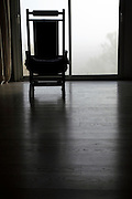 rocking chair in front of window looking out at a fogged up landscape view