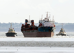 © Licensed to London News Pictures. Thames Estuary, Southend, Essex. 28th October 2013. The dredger, ARCO AXE, sits on the mudflats after being hit by the storm that hit the UK this morning. About 0650 this morning, ARCO AXE was struck by the gusts as she lay anchored off Southend. The severity of the gust caused her to drag the anchor and ended up stuck on the mud. There were no reported injuries and no damage caused. Two tugs have lines on her and waiting to try and refloat here at next high tide this evening.. Photo credit : Simon C Ford/LNP