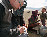 """Paul taking notes. Milking sheep herd. Life in Baiqara, a Wakhi High pasture inhabited for about 6 months of the year, from May until October. Guiding and photographing Paul Salopek while trekking with 2 donkeys across the """"Roof of the World"""", through the Afghan Pamir and Hindukush mountains, into Pakistan and the Karakoram mountains of the Greater Western Himalaya."""