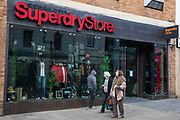 "Local residents walk past a branch of fashion chain Superdry on the second day of England's second coronavirus lockdown on 6 November 2020 in Windsor, United Kingdom. Only retailers selling ""essential"" goods and services are permitted to remain open to the public during the second lockdown but Superdry has reported a 52% increase in online sales in 2020."