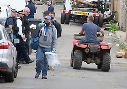 ©Licensed to London News Pictures 09/09/2020  <br /> Orpington, UK. A police officer with an evidence bag full of money and a policeman on a quad bike. Armed police have raided a travellers site in Orpington, South East London. Several hundred officers raided the site in the middle of the night and arrested people believed to be involved in supplying criminal gangs with firearms. Photo credit:LNP