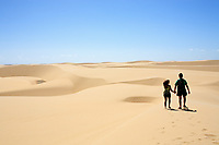 couple walking hand in hand on the desert sand dunes of the Lencois Maranheses National Park