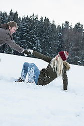 Young man helping his friend to stand up in snowy landscape, Bavaria, Germany