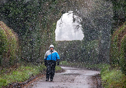 © Licensed to London News Pictures. 28/12/2020. London, UK. A walker braves the sleet and snow near Andover in Hampshire this afternoon as temperatures dropped to -3c in the South East today. The Met Office has issued a yellow weather warning for snow and ice for much of the country with heavy snow falls in Hampshire and the West Country. Photo credit: Alex Lentati/LNP