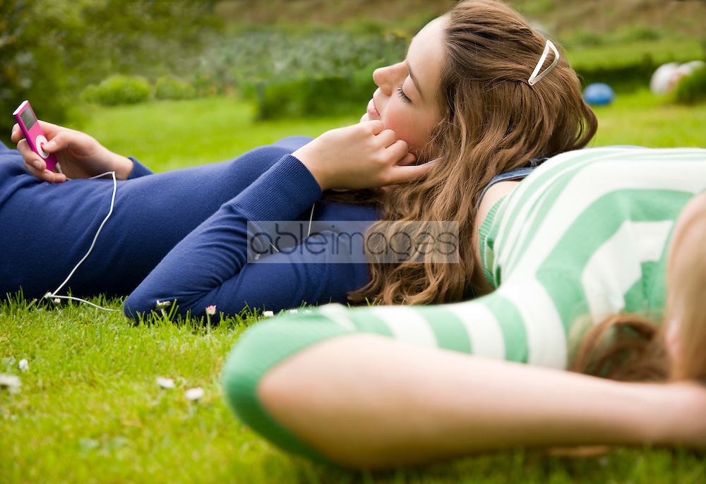 Teenaged girl holding mp3 player listening to music with head resting on friend waist