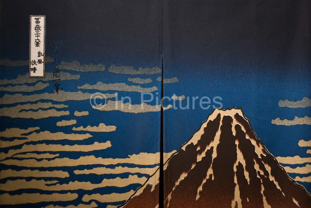 "A version of ""South Wind, Clear Sky"" by Hokusai, a view of the Fuji volcano, seen on a noren (a fabric panel) in Japanese entrepreneur, Tetsuro Hama's 'So' restaurant, Soho, London. Fine Wind, Clear Morning Gaifū kaisei, also known as South Wind, Clear Sky or Red Fuji, is wood block print by Japanese artist Hokusai (1760–1849), part of his Thirty-six Views of Mount Fuji series. It dates from about 1830–32, the Edo period. This is one of the Thirty-six Views of Mount Fuji Fugaku is an ukiyo-e series of large, color woodblock prints by the Japanese artist Katsushika Hokusai (1760–1849). The series depicts Mount Fuji in differing seasons and weather conditions from a variety of different places and distances."