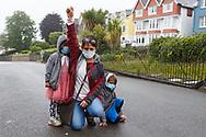Carmarthen, Carmarthenshire, Wales, UK. 18 July, 2020.<br /> A female protester with her young children, takes the knee in support of Black Lives Matter during a march in support of the removal of the Picton Monument in Carmarthen that commemorates General Thomas Picton, former Governor of Trinidad. <br /> Credit: Gruffydd Ll. Thomas