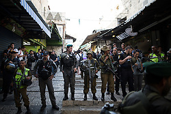 © Licensed to London News Pictures . 05/06/2016 . Jerusalem , Israel . Israeli soldiers block off the road in front of Damascus Gate to separate Israelis processing with flags from residents in the Old City's Muslim district . Israeli Jews celebrate Jerusalem Day . Photo credit : Joel Goodman/LNP