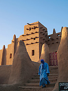 A man walks out of the Great Mosque of Djenné, the worlds largest mud built structure and UNESCO heritage site, Djenné, Mali