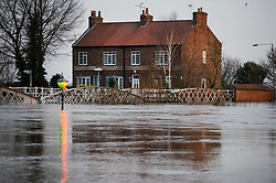 © Licensed to London News Pictures. 28/12/2015. Cawood, UK. A street light pokes above fold water in front of a property next to the river Ouse at Cawood in North Yorkshire where flood water and rising tides have threatened the town. Several warnings of risk to life are sill in place in parts of Lancashire and Yorkshire where rainfall has been unusually high, causing heavy flooding. Photo credit: Ben Cawthra/LNP