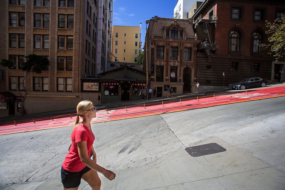 Een vrouw loopt een steile heuvel omhoog op Powell Street in San Francisco. De Amerikaanse stad San Francisco aan de westkust is een van de grootste steden in Amerika en kenmerkt zich door de steile heuvels in de stad.<br /> <br /> A woman walks a steep hill at Powell Street in San Francisco. The US city of San Francisco on the west coast is one of the largest cities in America and is characterized by the steep hills in the city.
