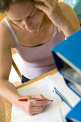Teacher struggling with the pressure of a backlog of homework to mark,