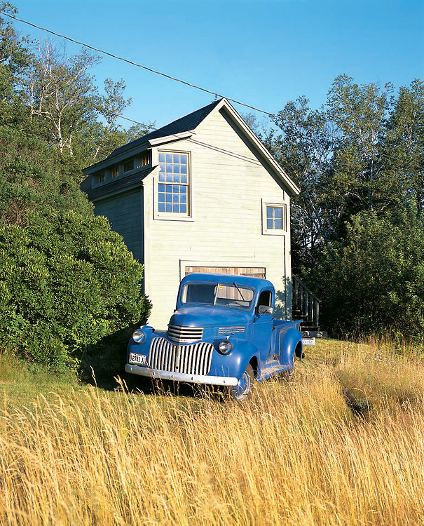 Modern guest house and vintage blue truck at country house in North Haven, Maine