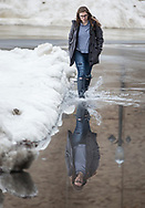 Kaleigh O'Boyle walks through a puddle near Notre Dame Stadium during a break in the rain on Monday.
