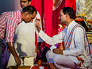 "23 SEPTEMBER 2018 - BANGKOK, THAILAND:  A Hindu priest gives a man a ""talika"" at the Ganesha Festival at Wat Dan in Bangkok. Ganesha Chaturthi also known as Vinayaka Chaturthi, is the Hindu festival celebrated on the day of the re-birth of Lord Ganesha, the son of Shiva and Parvati. The festival, also known as Ganeshotsav (""festival of Ganesha"") is observed in the Hindu calendar month of Bhaadrapada, starting on the the fourth day of the waxing moon. The festival lasts for 10 days, ending on the fourteenth day of the waxing moon. Outside India, it is celebrated widely in Nepal and by Hindus in the United States, Canada, Mauritius, Singapore, Thailand, Cambodia, and Burma.   PHOTO BY JACK KURTZ"