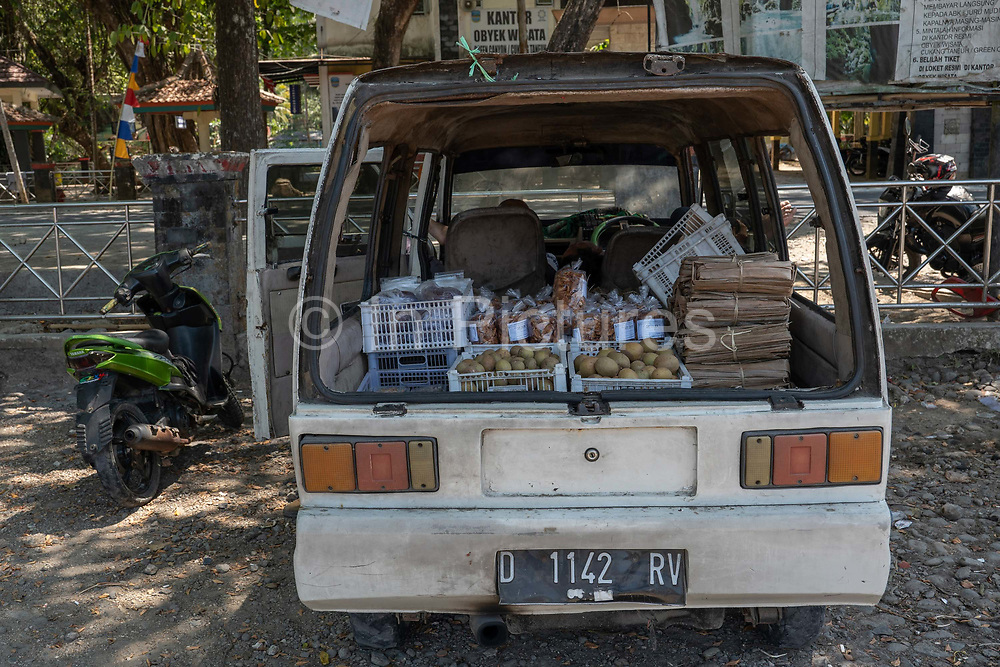 A beige van selling fruit and other consumable goods from the carboot at the Green Canyon carpark near Pangandaran on the 30th October 2019 in Java in Indonesia.
