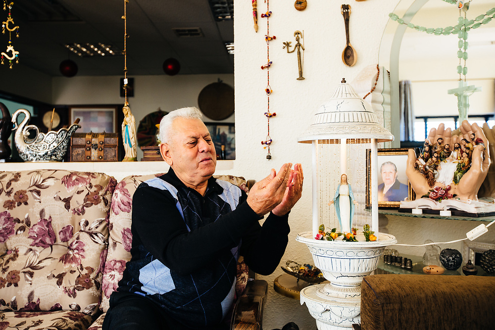Sami Bellan, owner of the Cana Guest House rubs olive oil on his hands next to a Virgin Mary figurine and other Christian ornaments and decorations, in the central part of the town of Kafr Kanna (Cana), the traditional site of Jesus' first miracle of turning water into wine, northern Israel, on December 9, 2017.