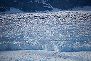 A helicopter flies nearly at sea level, close to the calving face of the Columbia Glacier, near Valdez, Alaska.