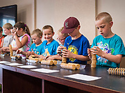 27 JUNE 2019 - CENTRAL CITY, IOWA: TUCKER HOTZ, 7, and other youngsters stack sandwich cream cookies during the cookie stacking contest at the Linn County Fair. Summer is county fair season in Iowa. Most of Iowa's 99 counties host their county fairs before the Iowa State Fair, August 8-18 this year. The Linn County Fair runs June 26 - 30. The first county fair in Linn County was in 1855. The fair provides opportunities for 4-H members, FFA members and the youth of Linn County to showcase their accomplishments and talents and provide activities, entertainment and learning opportunities to the diverse citizens of Linn County and guests.              PHOTO BY JACK KURTZ