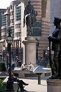 Londoners sit in warm spring sunshine beneath the WW1 war memorial and statue of the Duke of Wellington at Bank during a much quieter evening rush-hour during the third lockdown of the Coronavirus pandemic. Financial institutions and the Bank of England are located here, in the heart of the City of London, aka Square Mile, on 9th March 2021, in London, England.