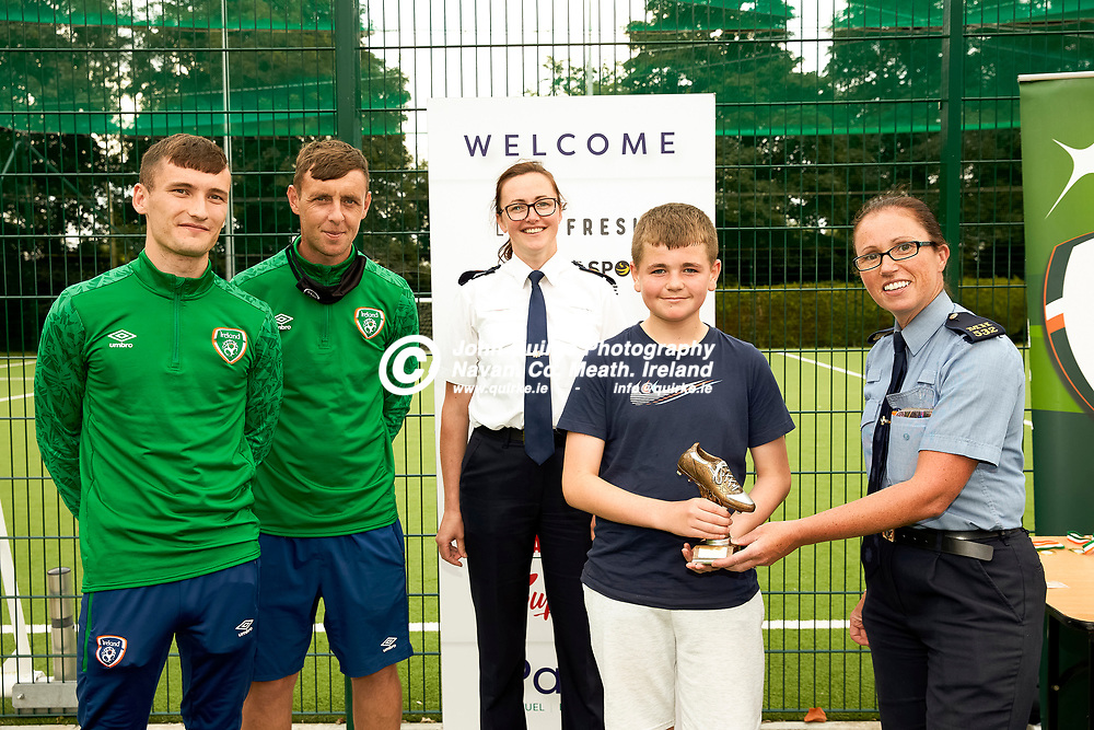 04-08-21, Garda youth diversion Soccer Initiative project in association with Meath Sports Partnership<br /> at Our Lady of Mercy school, Kells.<br /> Captain of the winning team, Jake Prior accepts the trophy from Sergeant Elaine Long. <br /> Also pictured are FAI representatives, Richard Smith, Conor Woods and Superintendent Thelma Watters<br /> Photo: David Mullen / www.quirke.ie ©John Quirke Photography, Proudstown Road Navan. Co. Meath. 046-9079044 / 087-2579454.<br /> ISO: 320; Shutter: 1/250; Aperture: 6.3;