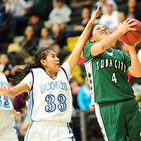 1212713  Adron Gardner/Independent<br /> <br /> Tuba City Warrior Samytha Parrish (4), right, attempts a layup ahead of Window Rock Scouts Shaniya Betsoi (33) and Naomie Klah (32) in Chinle Friday.