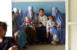 KABUL,AFGHANISTAN - AUGUST 29: Afghan women wait with their children to be seen by a doctor in the Indira Ghandi Hospital for Children August 29, 2002 in Kabul Afghanistan. The hospital has 300 beds but usually it is filled at double capacity with only 118 doctors. One in four children die before the age of 5 in Afghanistan. (Photo by Ami Vitale/Getty Images)