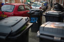 Wheelie bins waiting for collection block pavement