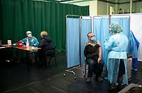 Siemiatycze, 19.04.2021. Punkt Szczepien Powszechnych w Siemiatyczach w hali sportowo-widowiskowej. Jest to jeden z 16 pilotazowych takich punktow w Polsce. Docelowo moze szczepic przeciwko COVID-19 500 osob dziennie. N/z podawanie szczepionki, z lewej kwalifikacja medyczna do szczepienia fot Michal Kosc / AGENCJA WSCHOD