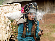 An elderly Akha Nuquie ethnic minority woman smokes tobacco with a pipe in Ban Huay Ou village, Phongsaly province, Lao PDR. One of the most ethnically diverse countries in Southeast Asia, Laos has 49 officially recognised ethnic groups although there are many more self-identified and sub groups. These groups are distinguished by their own customs, beliefs and rituals. Details down to the embroidery on a shirt, the colour of the trim and the type of skirt all help signify the wearer's ethnic and clan affiliations.