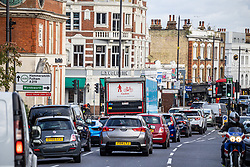 Licensed to London News Pictures. 24/10/2021. London, UK. Cars queue up at traffic lights crossing the South Circular at Putney today ahead of the ULEZ boundary expansion tomorrow. On Monday 25 October, the London Ultra-Low Emission Zone (ULEZ) area will expand to inside the North and South Circular with many drivers of older cars forced to pay a daily £12.50 fee or face heavy fines of £160.00. Photo credit: Alex Lentati/LNP