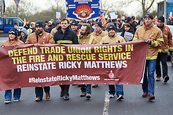 © Licensed to London News Pictures.  09/12/2014. AYLESBURY, UK. Thousands of fire fighters march through Aylesbury during the latest  nationwide strike of Fire Brigade Union members over pension rights. the union is also intending to take legal action over the dismissal of Ricky Matthews by the Buckinghamshire and Milton Keynes Fire Authority for taking part in pervious industry action. <br /> <br /> In this picture: Sacked firefighter Ricky Matthews (2nd left holding banner)<br /> <br /> Photo credit: Cliff Hide/LNP