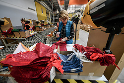 A worker gift wraps presents at Amazon's fulfillment centre in Swansea, in the run up to Black Friday.