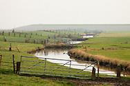 Buitendijks kweldergebied van waterschap Blija Buitendijks.<br /> Waterschap Blija Buitendijks is het kleinste waterschap van Nederland. Het waterschap beheert 100 hectare weiland, gelegen bij het dorp Blija in het noorden van Friesland, tussen de Waddenzeedijk en zomerdijk. Direct achter de 2,25 m +NAP hoge zomerdijk bevindt zich het uitgestrekte kweldergebied van de Waddenzee. Bij hoogwater (vloed) stroomt het buiten de zomerdijk gelegen kwelder regelmatig onder water. Bij extreem hoog water, bijvoorbeeld bij springtij en noordwesterstorm komt het zeewater vanuit de Waddenzee ook over de zomerdijk. De door het waterschap beheerde polder komt dan geheel onder water te staan, soms zelfs tot halverwege de Waddenzeedijk. Bij afgaand tij (eb) stroomt het zeewater via de klepstuwen in de zomerdijk terug naar de Waddenzee. <br /> De afgebeelde watergang (afwateringssloot) bevindt zich langs de zomerdijk met daarin de betonnen duikers met klepstuwen. Via de dammen in de watergang kunnen de veehouders vanaf hun weilanden op de zomerdijk en de daarachter gelegen kwelders komen. <br /> Op de achtergrond is de Waddenzeedijk (op Deltahoogte) te zien.