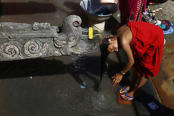July 27, 2017 - Lalitpur, Nepal - A woman takes a bath from a traditional water spout in Lalitpur, Nepal on Thursday. (Credit Image: © Skanda Gautam via ZUMA Wire)