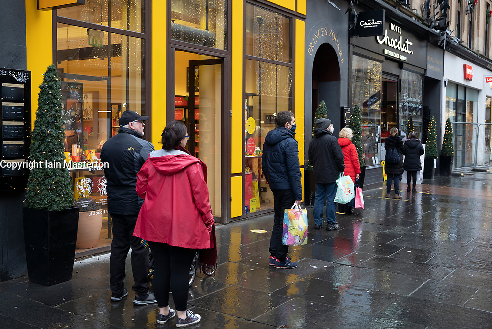 Glasgow, Scotland, UK. 11 December 2020. Covid-19 lockdown level 4 restrictions are lifted in Glasgow. Non essential businesses such as shops and restaurants can reopen from today. Pictured ;  Shoppers queue outside Hotel Chocolat on Buchan Street. ain Masterton/Alamy Live News
