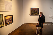 An elderly woman is visiting the exhibition space of The Sudeten German Museum in Munich. Its permanent exhibition spans 1100 years of history, art and cultural history, presented in authentic objects from its collections, on an exhibition area of 1200 square meters.