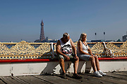 An older couple sit, looking exhausted, in the scorcing heat on one of Blackpools piers with the world famous Blackpool Tower in the background as temperatures in the country are expected to soar this week on 7th September, 2021 in Blackpool, United Kingdom. Temperatures in the UK are predicted to soar to highs of 29 degrees celsius, coinciding with a rise in daycation and staycation domestic tourism in the country as a result of Covid-19 precautions that make foreign travel increasingly costly and difficult.