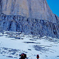 BAFFIN ISLAND, NUNAVUT, CANADA. Climbers approach towering cliff on Great Sail Peak, a route that will take 5 weeks to ascend.